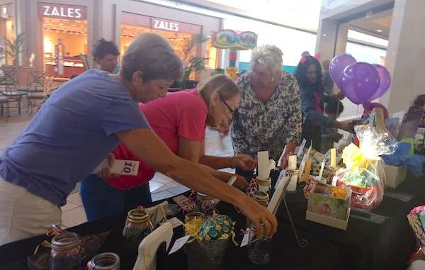 People looking at the raffle items at the Artisans at the Mall event.