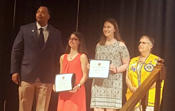Sebastian River High School Principle Dariyall Brown awards Stephanie Giordano and Reagan O'Rourke scholarships with a representative from The Lions club.