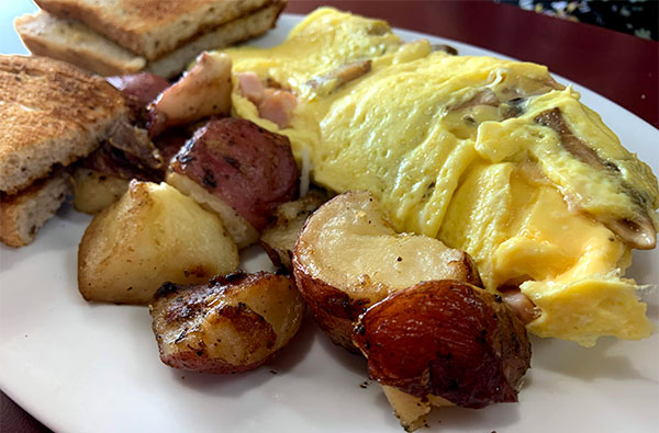 Ham, mushroom, and cheese omelet with home fries and rye toast.