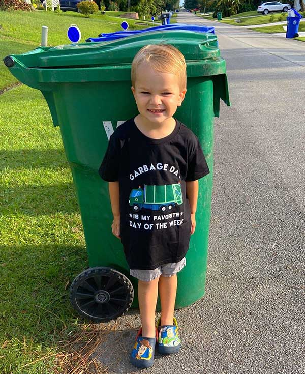 """Roman wears a t-shirt that reads """"Garbage Day Is My Favorite Day of the Week."""