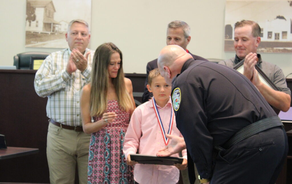 Chief Dan Acosta presents Hero Award to Gage Kepley
